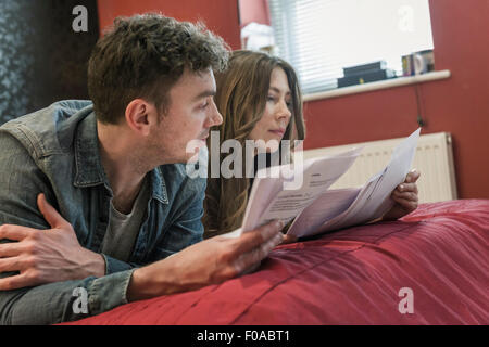 Couple lying on bed looking at paperwork - Stock Photo