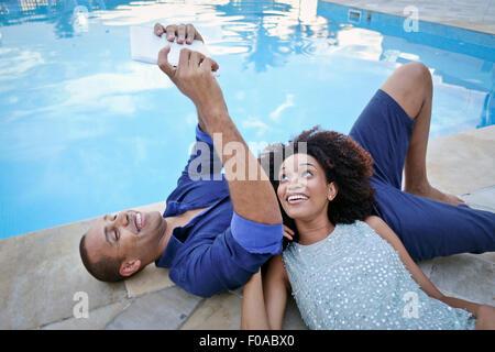 Stylish couple taking digital tablet selfie on poolside, Rio De Janeiro, Brazil - Stock Photo