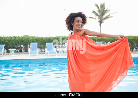 Portrait of young woman wearing orange dress at hotel poolside, Rio De Janeiro, Brazil - Stock Photo