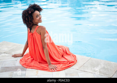 Portrait of young woman wearing orange dress sitting at hotel poolside, Rio De Janeiro, Brazil - Stock Photo