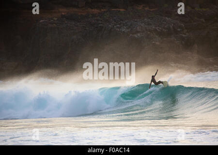 Silhouetted young man surfing wave at sunset, Fuerteventura, Spain - Stock Photo