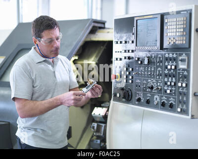Engineer measuring part in front of CNC lathe - Stock Photo