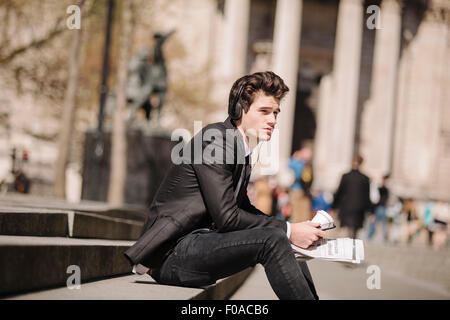 Young city businessman with newspaper sitting on bench listening to headphones - Stock Photo