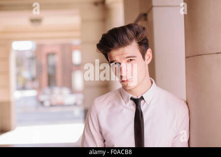 Portrait of confident young city businessman leaning against pillar - Stock Photo