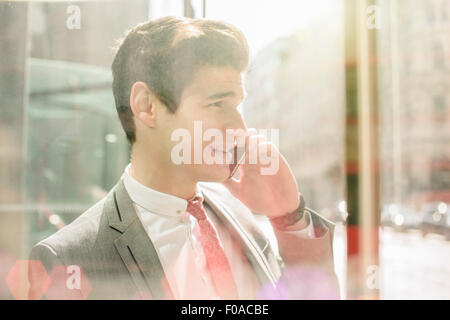 Young city businessman chatting on smartphone in doorway - Stock Photo