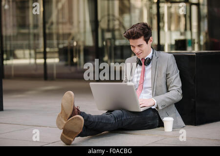 Young city businessman sitting on sidewalk using laptop - Stock Photo