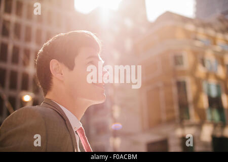 Young city businessman looking up in sunlight - Stock Photo