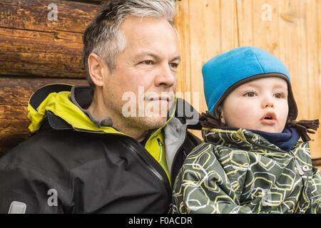 Father and son sitting together, outdoors, looking away - Stock Photo