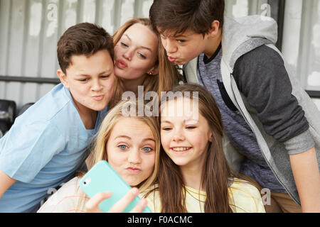 Five boys and girls making faces for smartphone selfie in shelter - Stock Photo