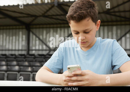 Boys texting on smartphone - Stock Photo