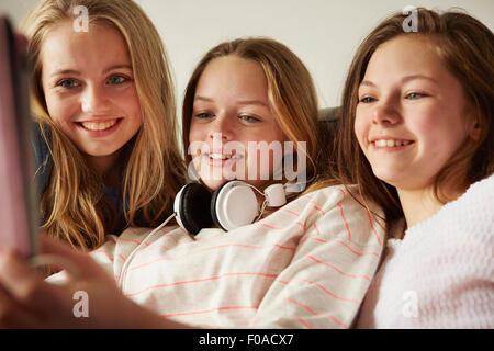 Three girls on sofa using digital tablet - Stock Photo