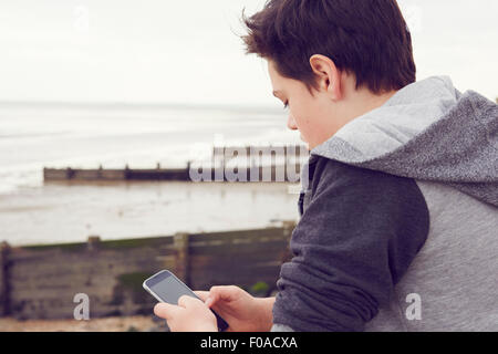 Teenage boy at seaside texting on smartphone, Southend on Sea, Essex, UK - Stock Photo