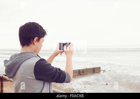 Teenage boy photographing sea on smartphone, Southend on Sea, Essex, UK - Stock Photo