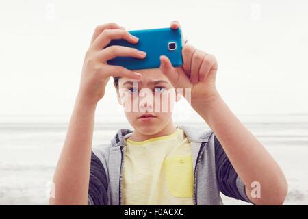 Teenage boy taking smartphone selfie at seaside, Southend on Sea, Essex, UK - Stock Photo