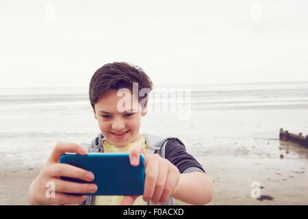 Smiling teenage boy taking smartphone selfie at seaside, Southend on Sea, Essex, UK - Stock Photo