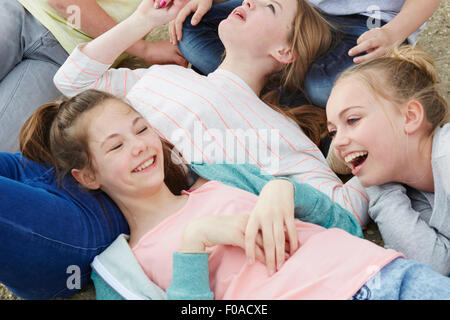 Cropped view of five boys and girls lying on ground - Stock Photo