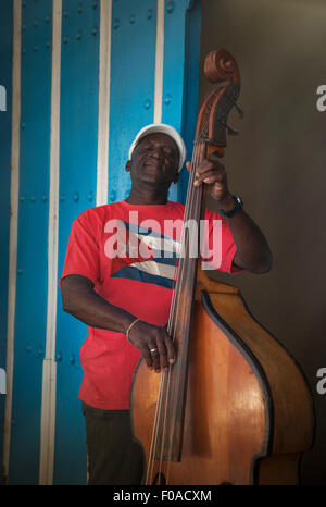 Senior man playing double bass in front of blue wall, Santiago de Cuba, Cuba