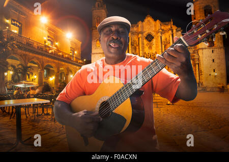 Senior man playing acoustic guitar in Plaza de la Cathedral at night, Havana, Cuba - Stock Photo