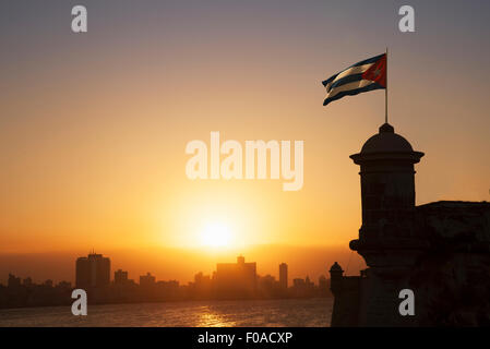 Cuban flag over the Fortress of El Morro at sunset, Havana, Cuba - Stock Photo