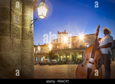 Senior man playing double bass in Plaza de la Cathedral at night, Havana, Cuba - Stock Photo