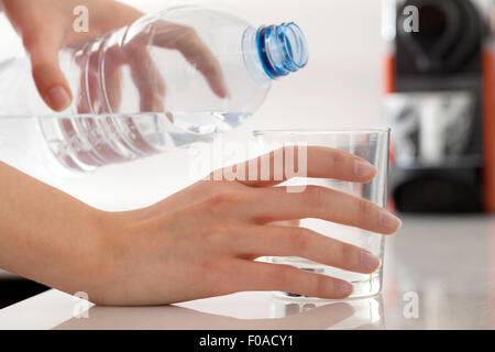 Female hands pouring bottled water into glass - Stock Photo