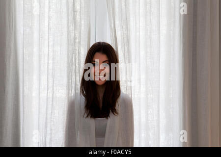 Young adult woman poking head out of curtains - Stock Photo