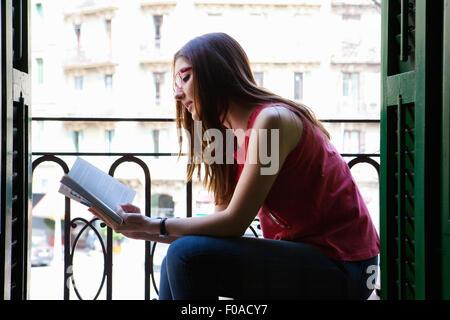 Young adult female sitting on balcony reading - Stock Photo