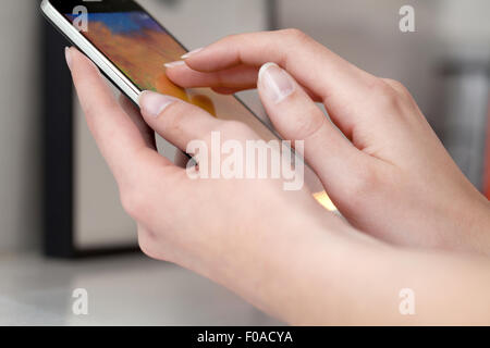 Female hands using smartphone - Stock Photo
