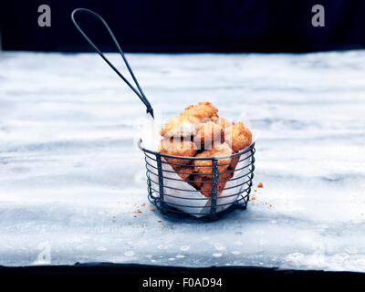 Frying basket full of breaded Scottish wholetail scampi - Stock Photo