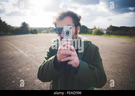 Portrait of mid adult man pointing vintage movie camera on waste ground