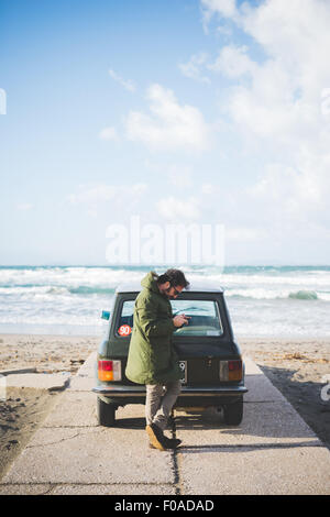 Man with vintage car parked on beach reading smartphone texts, Sorso, Sassari, Sardinia, Italy - Stock Photo