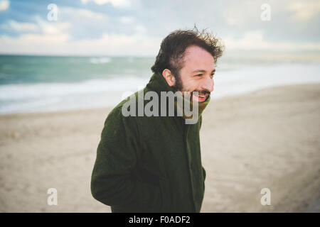 Portrait of mid adult man on windy beach, Sorso, Sassari, Sardinia, Italy - Stock Photo