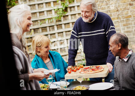 Senior man serving friends pizza in garden - Stock Photo