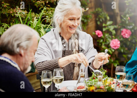 Senior friends eating meal in garden - Stock Photo