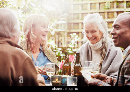 Senior friends playing cards in garden - Stock Photo