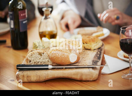 Freshly baked bread on breadboard, close up - Stock Photo