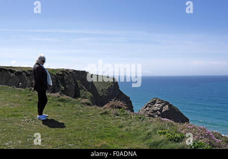 FEMALE STANDING ON A CLIFF EDGE. CORNWALL UK. - Stock Photo