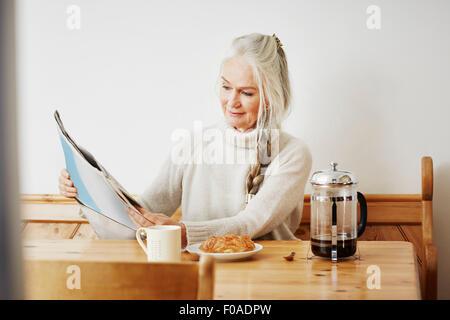 Senior woman reading newspaper at breakfast - Stock Photo
