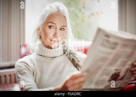 Senior woman reading newspaper - Stock Photo