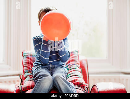 Young boy holding balloon in front of face - Stock Photo