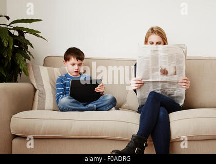 Young boy using digital tablet, mother reading newspaper - Stock Photo