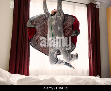 Young boy wearing cape jumping on bed - Stock Photo