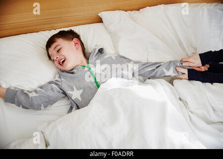 Mother pulling son out of bed - Stock Photo
