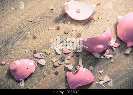 Broken piggy bank and coins - Stock Photo