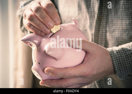 Man inserting coin into piggy bank - Stock Photo