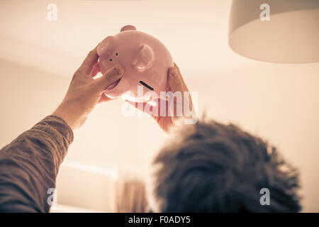 Man looking up at piggy bank - Stock Photo