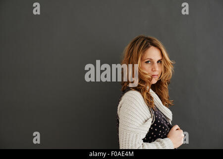 Mid adult woman side view looking at camera - Stock Photo