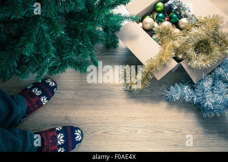 Person wearing slippers with christmas decorations, high angle - Stock Photo