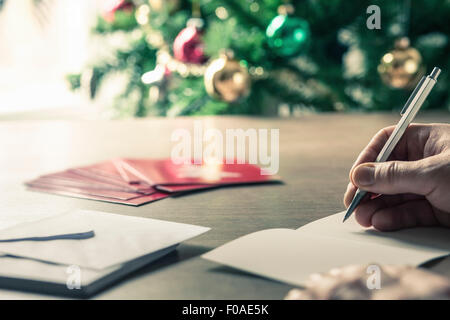 Person writing christmas cards - Stock Photo