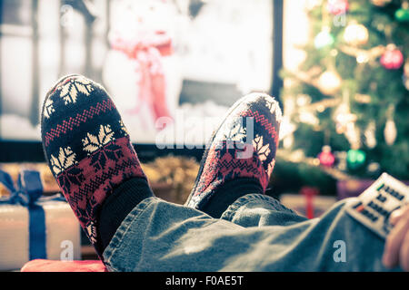 Person wearing slippers with feet up - Stock Photo